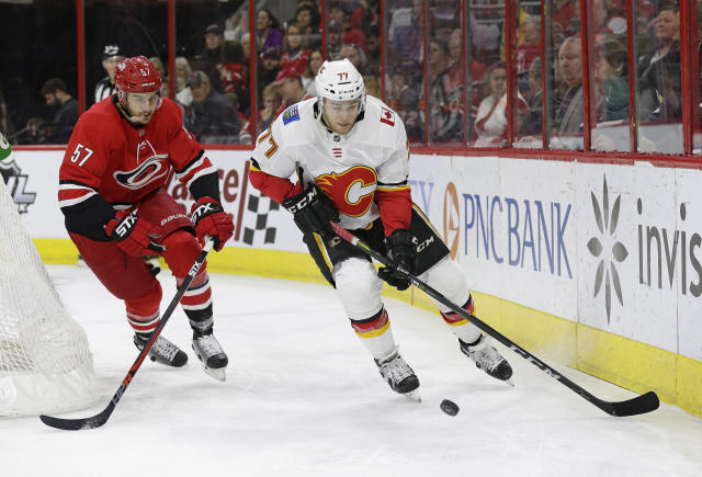 Carolina Hurricanes' Trevor van Riemsdyk (57) chases the puck with Calgary Flames' Mark Jankowski (77) during the first period of an NHL hockey game in Raleigh, N.C., Sunday, Feb. 3, 2019. (AP Photo/Gerry Broome)