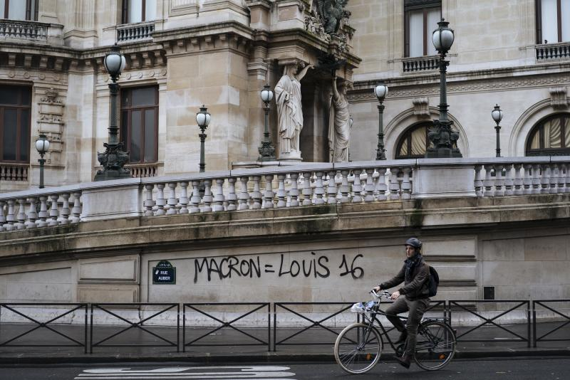 "FILE - In this Dec. 2, 20118 file photo, a man rides his bicycle past by a graffiti on the Paris Garnier Opera house in Paris that reads: ""Macron is equal to Louis 16"", referring to the King of France during the French Revolution in 1789. There are parallels for unpopular French President Emmanuel Macron in the demise of King Louis XVI more than two centuries ago. Democracy has replaced monarchy but the culture of a mob taking its anger against perceived inequality onto the streets of Paris has not changed. (AP Photo/Kamil Zihnioglu, File)"