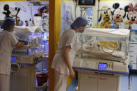 A Moroccan nurse takes care of one of the nine babies protected in an incubator at the maternity unit of the Ain Borja clinic in Casablanca, Morocco, Thursday May 20, 2021, two weeks after Mali's Halima Cisse, 25, gave birth to nine healthy babies. (AP Photo / Abdeljalil Bounhar)