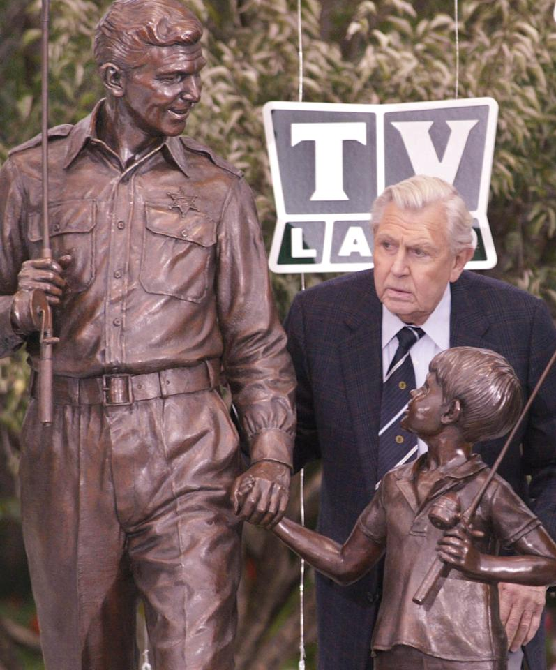 Andy Griffith gets a closer look at a bronze statue of Andy and Opie honoring The Andy Griffith television show Tuesday, Oct. 28, 2003, after the statue was unveiled during a ceremony in Raleigh, N.C.  Griffith's 40-year acting career has been largely defined by Sheriff Andy Tayor, a character he played in the show.(AP Photo/Bob Jordan)