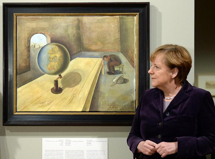 """German chancellor Angela Merkel poses by a painting """"The Refugee"""" by Felix Nussbaum on January 25, 2016 in Berlin during the opening of the exhibition """"Art from the Holocaust -100 Works from the Yad Vashem Collection"""" at the History museum in Berlin (AFP Photo/Britta Pedersen)"""