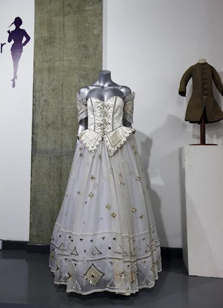 A 1986 Emanuel ball gown worn by late Princess Diana is displayed on a mannequin during an auction in London, Tuesday, Dec. 3, 2013. According to the auction house, Diana wore the gown with gold sequins, crystals and pearl beads comes with matching headband, optional sleeve panels and petticoat, in various occasions. (AP Photo/Lefteris Pitarakis)