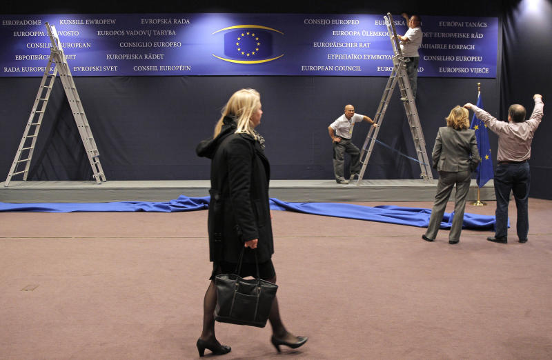Workers adjust a billboard at the European Council building in Brussels, Monday, Nov. 11, 2013. U.S. and European negotiating teams resumed talks Monday on what could become the biggest trade agreement in history: the Transatlantic Trade and Investment Partnership. (AP Photo/Yves Logghe)
