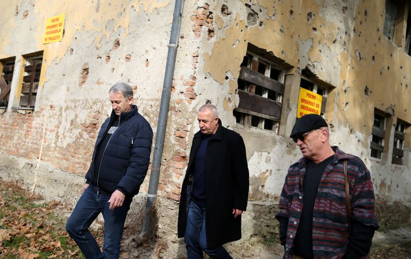 War veterans Boro Jevtic (L-R), Marko Zelic and Rizo Salkic walk past a house destroyed during the Bosnian War in Maglaj