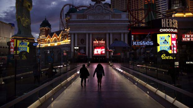 People walk along the Las Vegas Strip devoid of the usual crowds after casinos were ordered to shut down due to the coronavirus outbreak, Wednesday, March 18, 2020, in Las Vegas