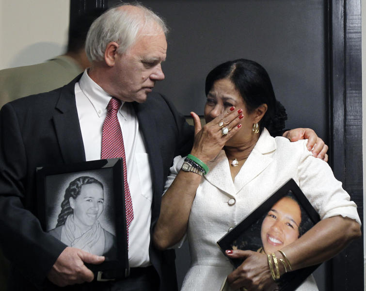 Nicolas and Virginia Payne, of New Milford, Conn., react as they hold pictures of their slain daughter, Rebecca, outside a Suffolk Superior Courtroom in Boston, Monday, June 18, 2012, after Cornell Smith, 30, was arraigned on first-degree murder charges in her shooting death in her Boston apartment. (AP Photo/Elise Amendola)