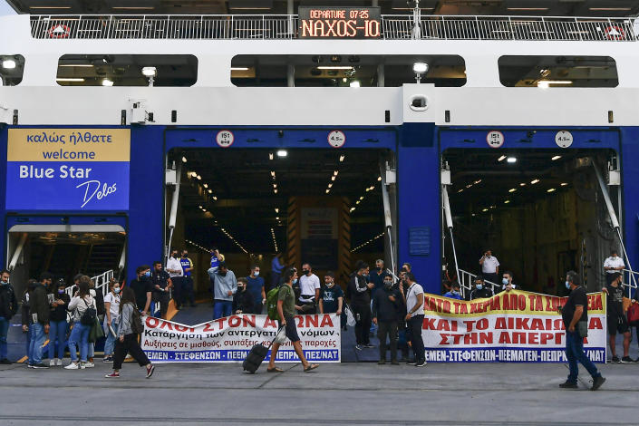 A passenger walks past protesters blocking the entrance of a passenger ferry during a 24-hour labour strike at the port of Piraeus, near Athens, Thursday, June 10, 2021. Greece's biggest labor unions stage a 24-hour strike to protest a draft labor bill being debated in parliament, which workers say will erode their rights. (AP Photo/Michael Varaklas)