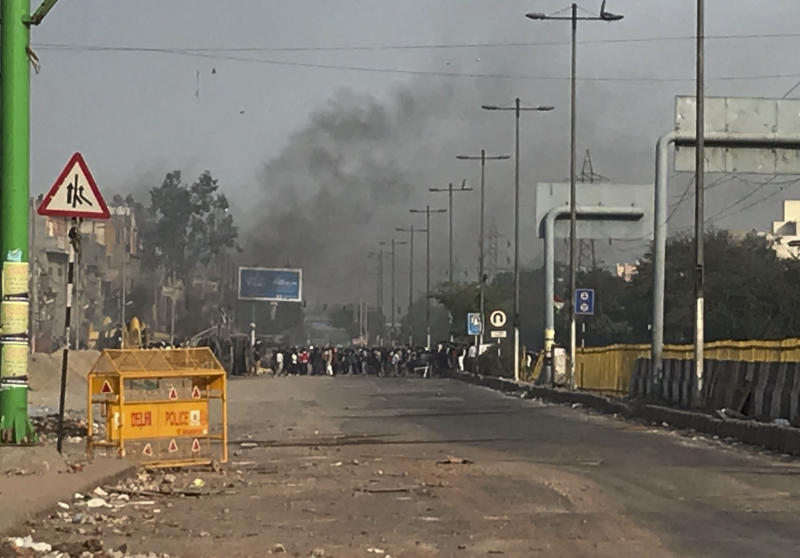 A mob throws stones as smoke rises from buildings set on fire following violence between two groups in New Delhi, India, Tuesday, Feb. 25, 2020. At least seven people, including a police officer, were killed and dozens injured in the clashes, police said Tuesday. (AP Photo/Rishabh. R. Jain)