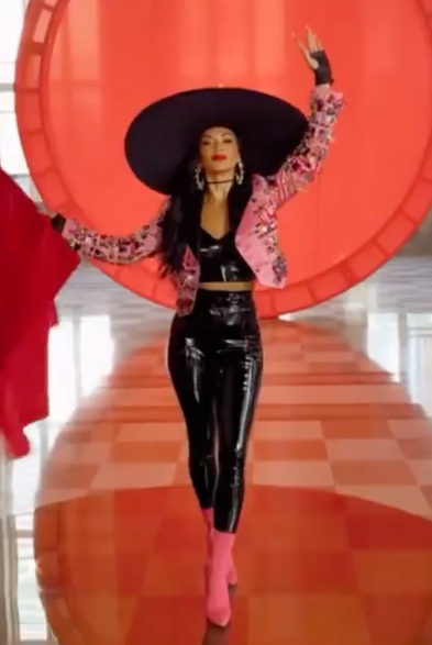 Nicole Scherzinger wearing a black PVC crop top and pants and a bolero jacket and a wide-brimmed hat for a new music video for the song