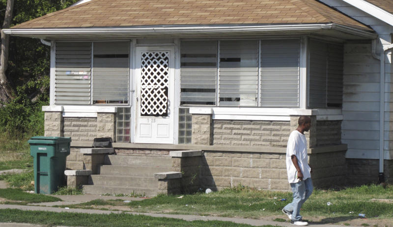 A man passes by a Washington Park, Ill., home Friday, Aug. 24, 2012, where a 19-year-old St. Louis woman claims she was held captive for more than three years before managing to escape on Monday, Aug. 20 and notify police. Authorities who raided the southwestern Illinois house Thursday arrested a 25-year-old man and his mother while retrieving a 2-year-old boy the teenager said was the result of nearly daily sexual attacks she endured at the home. (AP Photo/Jim Suhr)
