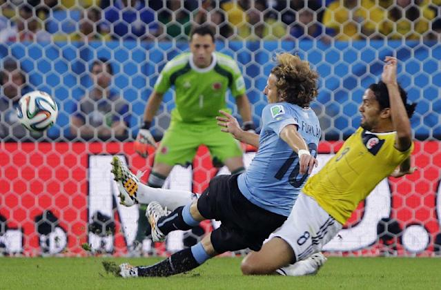 Uruguay's Diego Forlan, left, is challenged by Colombia's Abel Aguilar as he gets in a shot during the World Cup round of 16 soccer match between Colombia and Uruguay at the Maracana Stadium in Rio de Janeiro, Brazil, Saturday, June 28, 2014. (AP Photo/Sergei Grits)
