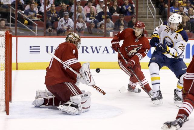 Phoenix Coyotes' Thomas Greiss (1), of Germany, makes a save on a shot by Buffalo Sabres' Matt Moulson (26) as Coyotes' Antoine Vermette (50) defends during the first period of an NHL hockey game on Thursday, Jan. 30, 2014, in Glendale, Ariz. (AP Photo)
