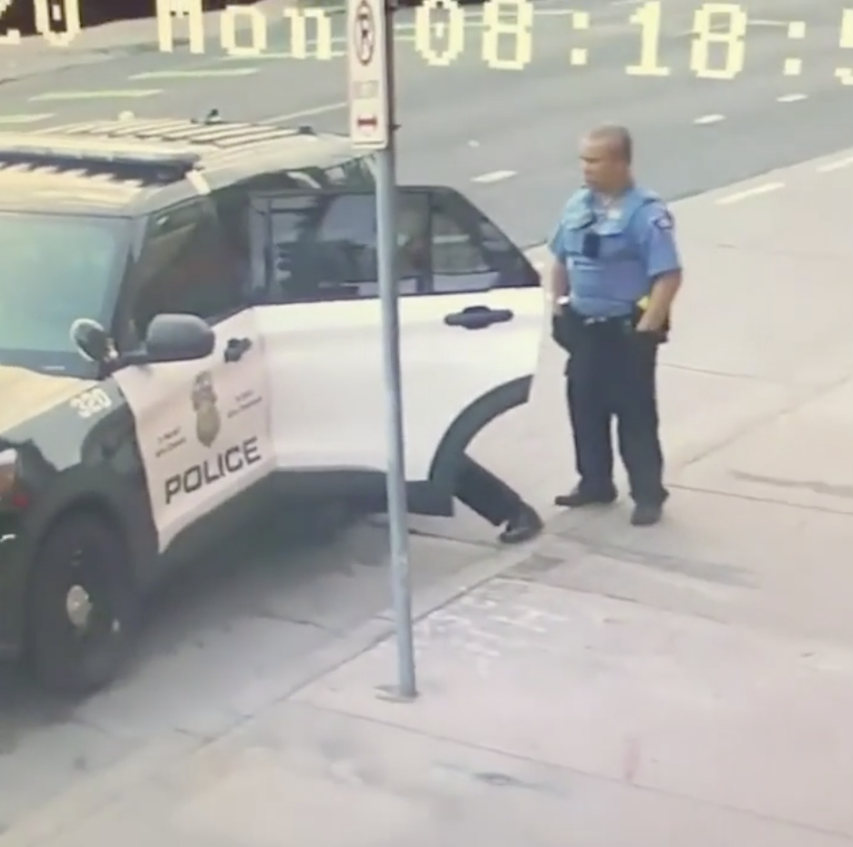Minneapolis police officers are pictured standing at their police car in CCTV footage.