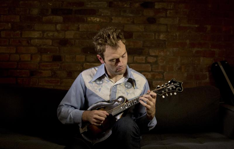 """In this Sept. 17, 2012 photo provided by the Chicago-based John D. and Catherine T. MacArthur Foundation, Chris Thile, 31, a mandolinist and composer who is creating a new musical aesthetic and a distinctly American canon for the mandolin through a lyrical fusion of traditional bluegrass orchestrations with a range of styles and genres, is seen in his East Village apartment in New York. Thile is among 23 recipients of this year's MacArthur Foundation """"genius grants."""" (AP Photo/Courtesy of theJohn D. and Catherine T. MacArthur Foundation, Christopher Lane)"""