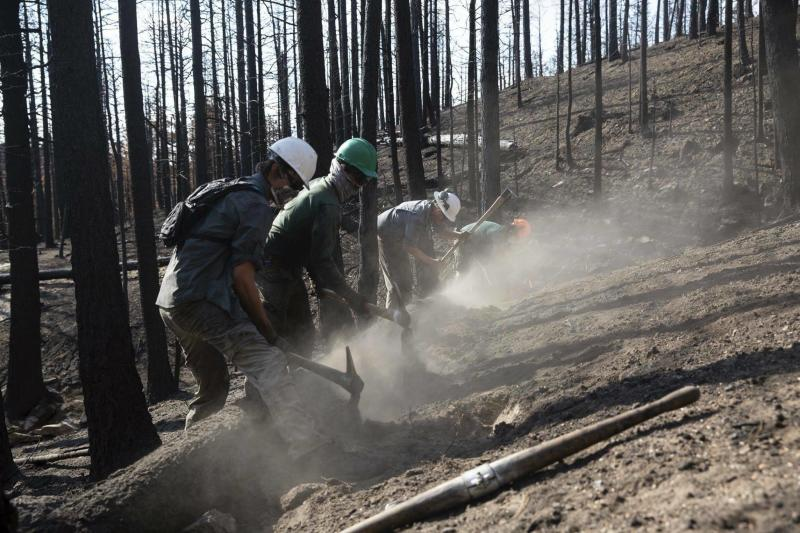 This undated photo provided by the Philmont Scout Ranch shows members of the Philmont Recovery Corps building a series of contours on a charred hillside to limit erosion. The historic ranch near Cimarron, New Mexico, is rebuilding following a devastating wildfire that burned nearly 44 square miles in 2018. Backcountry trails were wiped out along with trail camps. (Shane Mrozek/Philmont Scout Ranch via AP)