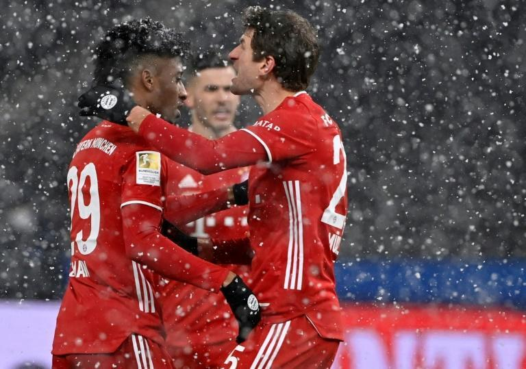 Kingsley Coman (L) celebrates with Thomas Mueller after putting Bayern Munich in front against Hertha Berlin in the snow in the German capital