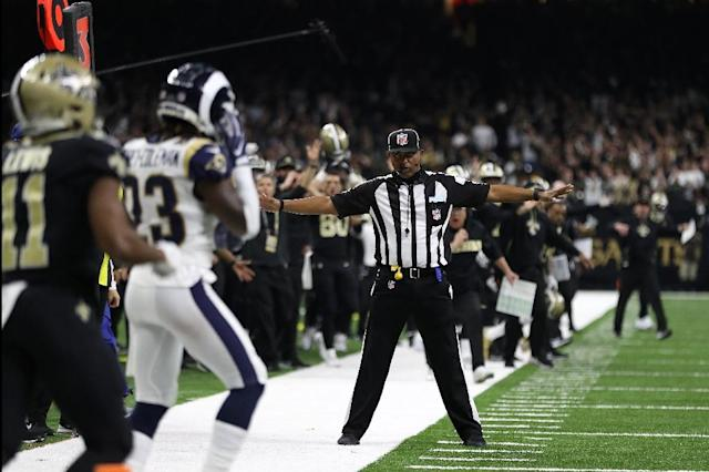 "Referees such as the one who signals only an incomplete pass on this controversial play involving the New Orleans Saints and Los Angeles Rams would have backup help from a ""sky judge"" under a proposal being considered by the NFL Competition Committee (AFP Photo/Chris Graythen)"