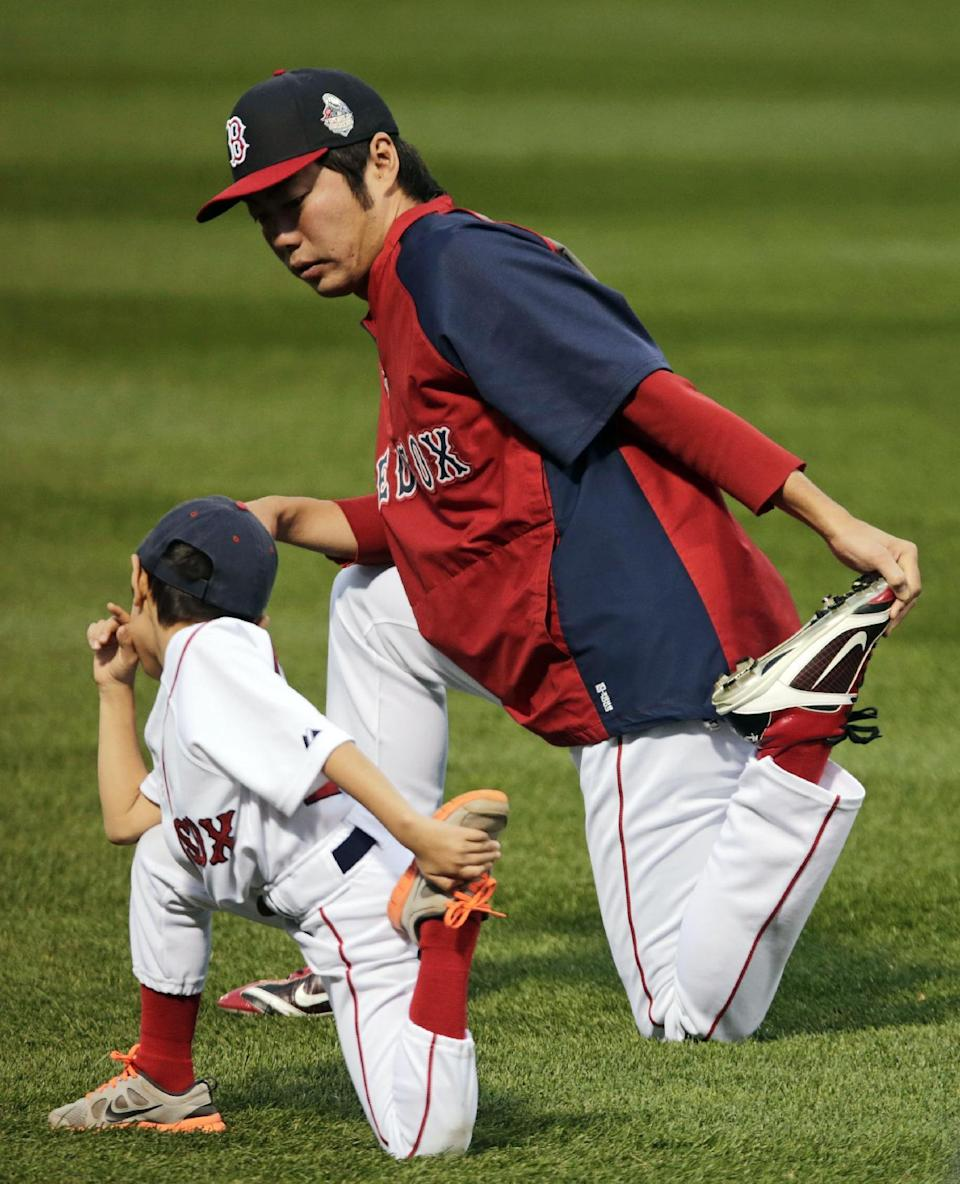 Boston Red Sox's Koji Uehara, of Japan, stretches with his son Kazuma, during a workout out Fenway Park Tuesday, Oct. 22, 2013, in Boston. The Red Sox are scheduled to host the St. Louis Cardinals in Game 1 of baseball's World Series on Wednesday. (AP Photo/Charles Krupa)