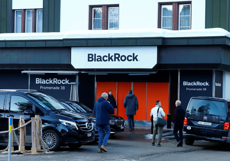 People are seen in front of a showroom that hosts BlackRock in Davos