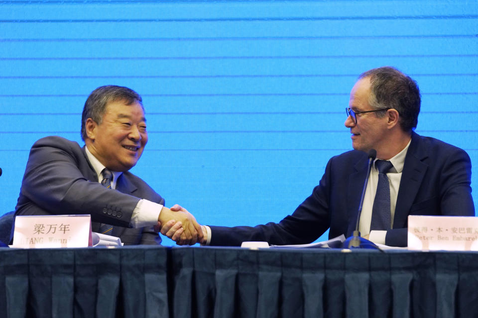 Peter Ben Embarek, of the World Health Organization team, right, shakes hands with his Chinese counterpart Liang Wannian after a WHO-China Joint Study Press Conference held at the end of the WHO mission in Wuhan, China, Tuesday, Feb. 9, 2021. (AP Photo/Ng Han Guan)