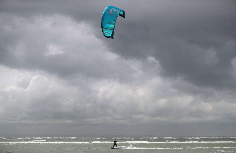 A kite surfer enjoys the strong winds on West Wittering beach in West Sussex. Storm Hannah is set to bring strong winds and much cooler conditions to the UK, with temperatures expected to plunge more than 10 degrees in some parts.