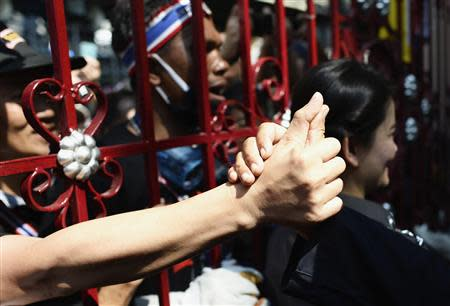 An anti-government protester touches hand of police officer through main gate of Thai Police Headquarters in Bangkok