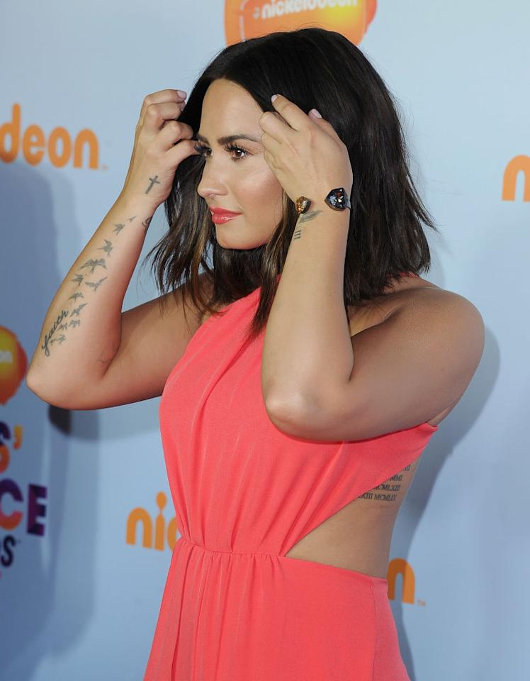 <p>Lovato adjusts her hair on the red carpet. (Photo: Getty Images) </p>