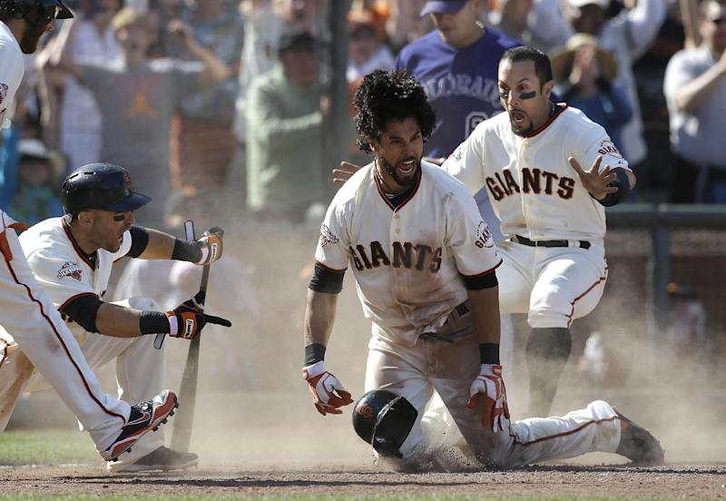 San Francisco Giants' Angel Pagan, center, celebrates with Marco Scutaro, left, and Andres Torres after hitting an inside the park two-run home run off of Colorado Rockies pitcher Rafael Betancourt during the 10th inning of a baseball game in San Francisco, Saturday, May 25, 2013. The Giants won 6-5 in 10 innings. (AP Photo/Jeff Chiu)