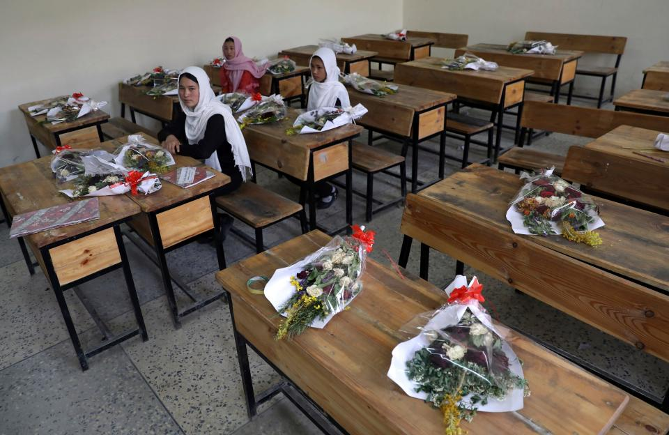 Schoolgirls sit inside a classroom with bouquets of flowers on empty desks as a tribute to those killed in the brutal May 8 bombing of the Syed Al-Shahda girls school, in Kabul, Afghanistan, Sunday, May 16, 2021. On Sunday parents of scores of young girls killed in the bombing demonstrated in the mostly Shiite neighborhood of Dasht-e-Barchi to demand the government provide them with greater security. They said 90 people were killed.