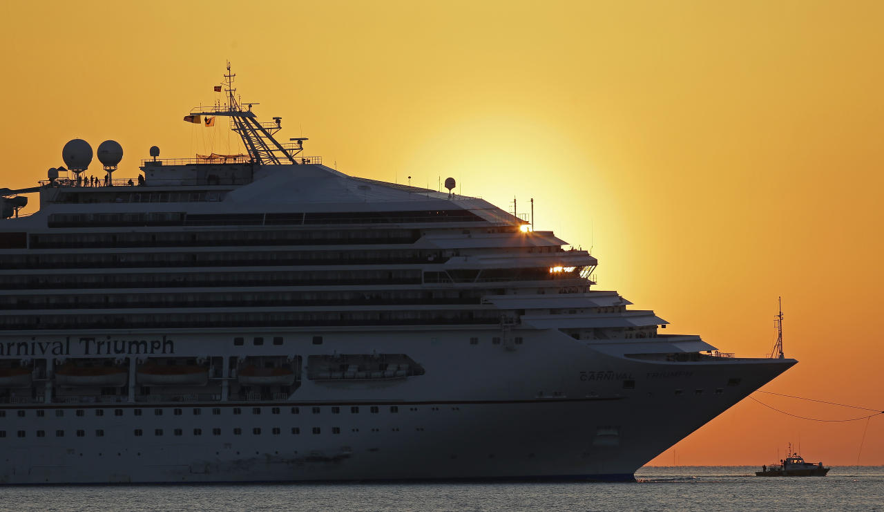 The cruise ship Carnival Triumph is towed into Mobile Bay near Dauphin Island, Ala., Thursday, Feb. 14, 2013. The ship with more than 4,200 passengers and crew members has been idled for nearly a week in the Gulf of Mexico following an engine room fire. (AP Photo/Dave Martin)