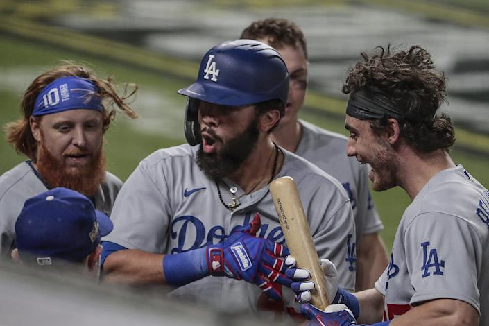 Edwin Ríos celebrates with his Dodgers teammates after hitting a solo home run in Game 4 of the NLCS.