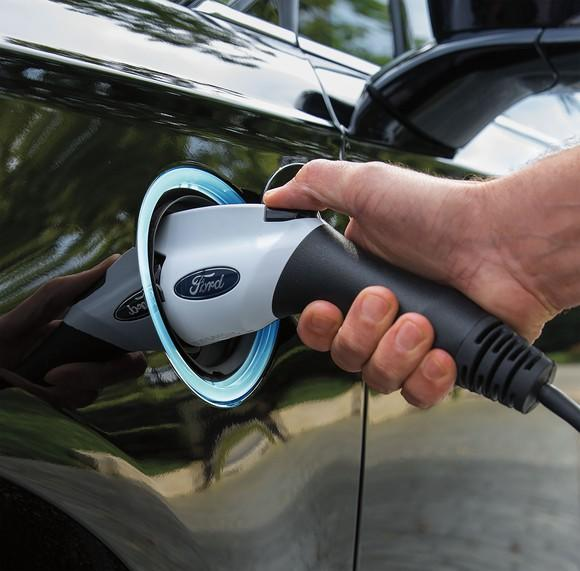 A Ford-branded electric charging plug is shown plugged into a Ford Fusion Energi plug-in hybrid sedan.