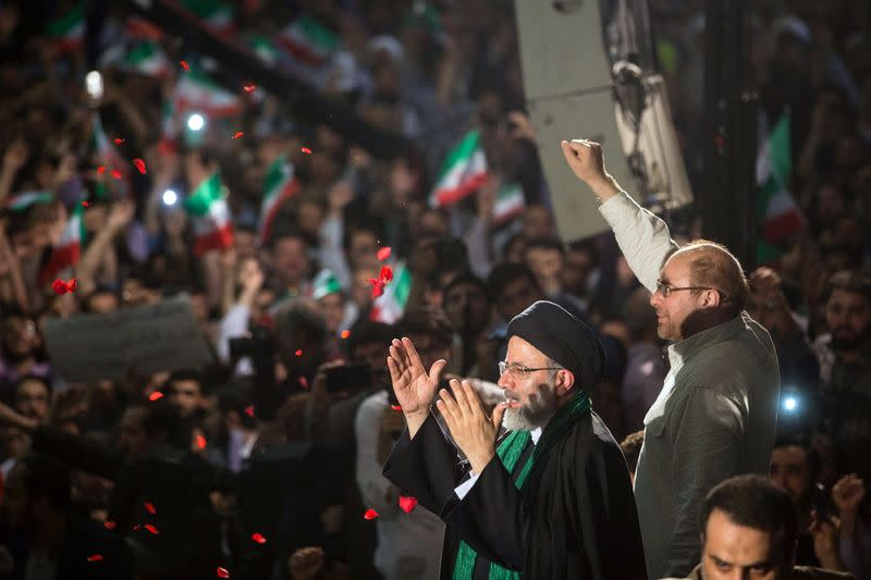Iranian Presidential candidate Ebrahim Raisi and Tehran Mayor Mohammad Baqer Qalibaf gesture during a campaign meeting at the Mosalla mosque in Tehran