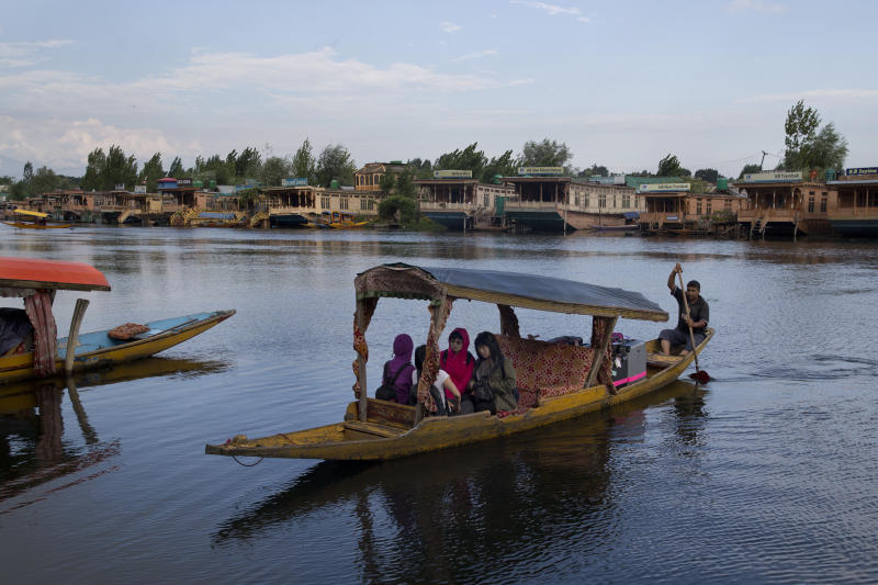 FILE - In this Saturday, Aug. 3, 2019, file photo, Foreign tourists cross the Dal Lake on a Shikara as they prepare to leave Srinagar, Indian controlled Kashmir. Authorities in Indian-controlled Kashmir are allowing tourists back into the region two months after ordering them to leave, citing security concerns. The local government had instructed tourists and Hindu pilgrims to leave on Aug. 2, three days before India stripped the Muslim-majority region of its statehood and special semi-autonomous status. (AP Photo/Dar Yasin, File)