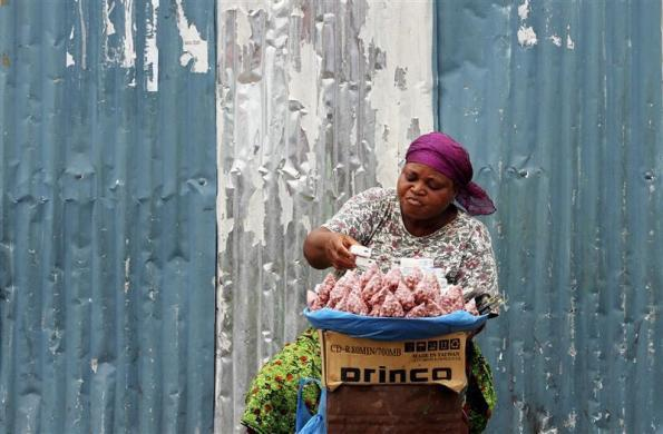 A street vendor sells her goods on a street near the Libreville bus station in Gabon, February 14, 2012.