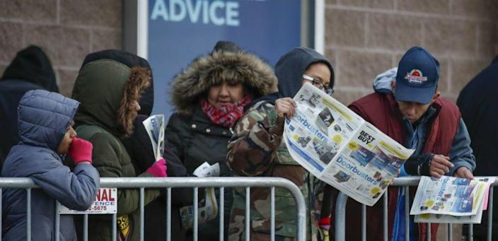 People wait outside a Best Buy behind a metal fence before the store opens their door for Black Friday on November 22, 2018.