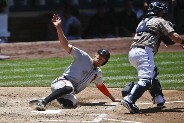 San Francisco Giants' Hunter Pence slides past San Diego Padres catcher Yasmani Grandal while scoring in the third inning of a baseball game Sunday, July 6, 2014, in San Diego. Pence scored on a double by Joe Panik. (AP Photo/Lenny Ignelzi)
