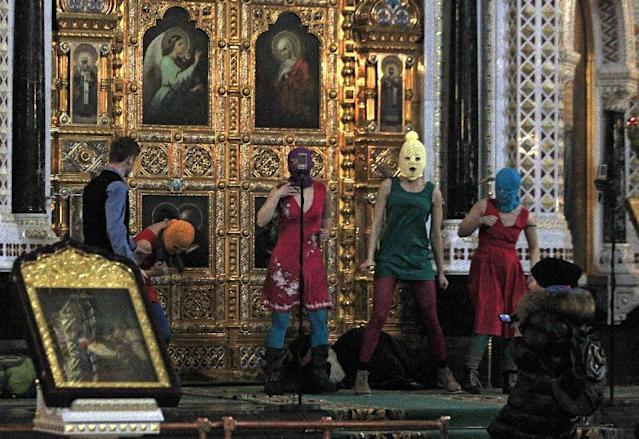 "FILE - In this Feb. 21, 2012 file photo, members of the Russian radical feminist group Pussy Riot try to perform at the Christ the Saviour Cathedral in Moscow. The trial of feminist punk rockers who chanted a ""punk prayer"" against President Vladimir Putin from the pulpit of Russia's largest cathedral started in Moscow Friday, July 20, 2012 amid controversy over the prank that divided devout believers, Kremlin critics and ordinary Russians. (AP Photo/Sergey Ponomarev, File)"
