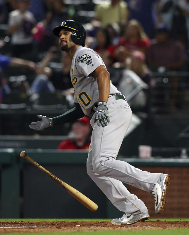 Oakland Athletics Marcus Semien (10) drops his bat as he watches his home run shot against the Texas Rangers that broke the tie in the ninth inning of a baseball game Monday, April 23, 2018, in Arlington, Texas. (AP Photo/Richard W. Rodriguez)