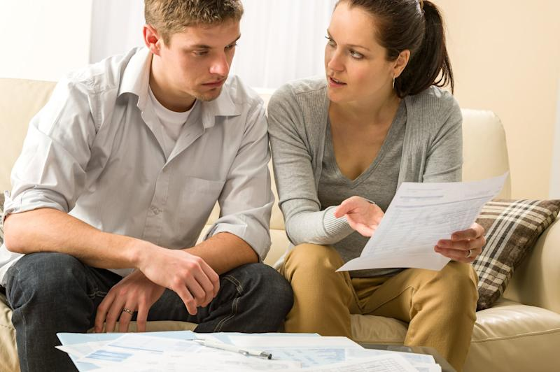 Couple looking at bills in dismay.