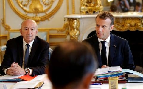 French President Emmanuel Macron sits next to Interior Minister Gerard Collomb as he leads a cabinet meeting - Credit: REUTERS