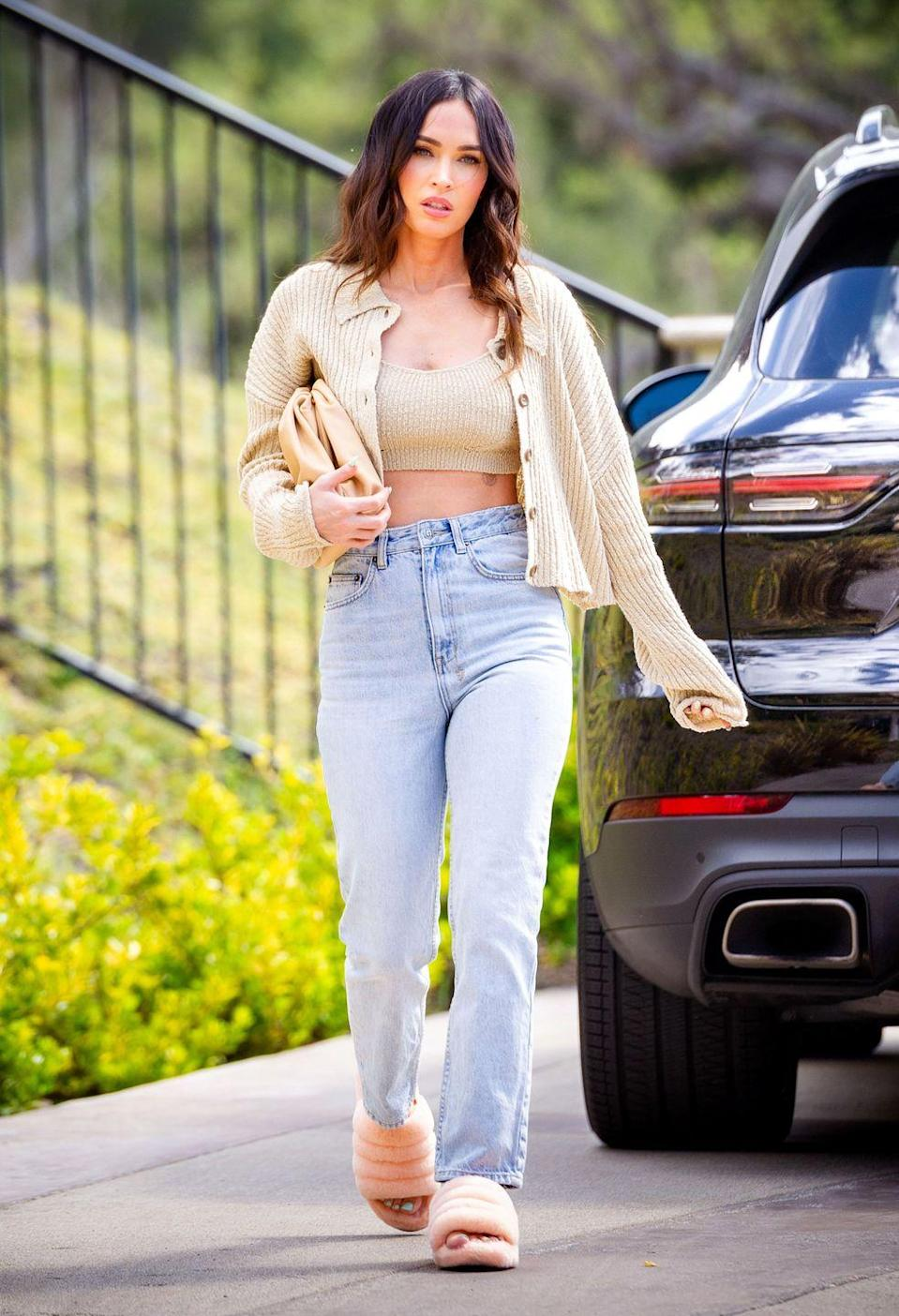 <p>The star wore a pair of peach-coloured UGG sliders, jeans, a beige-hued crop top and knitted cardigan from Urban Outfitters while out in Los Angeles. </p>