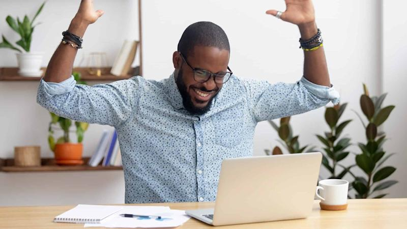 Happy man sits in front of laptop with arms up in celebration