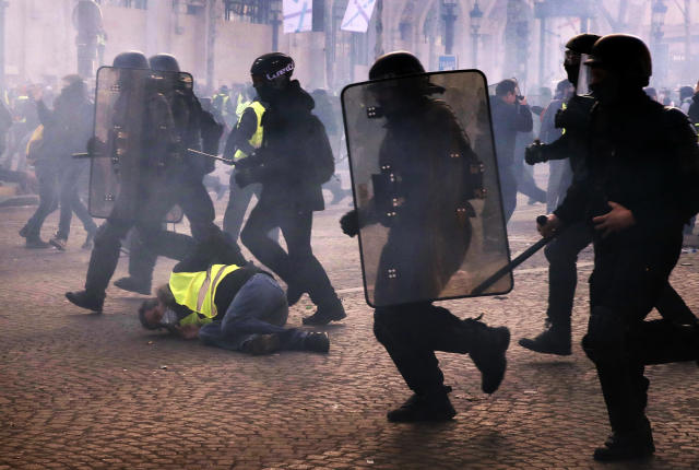 Riot police officers charge as a yellow vests demonstrator falls Saturday, March 16, 2019 in Paris. Paris police say more than 100 people have been arrested amid rioting in the French capital by yellow vest protesters and clashes with police. They set life-threatening fires, smashed up luxury stores and clashed with police firing tear gas and water cannon (AP Photo/Christophe Ena)
