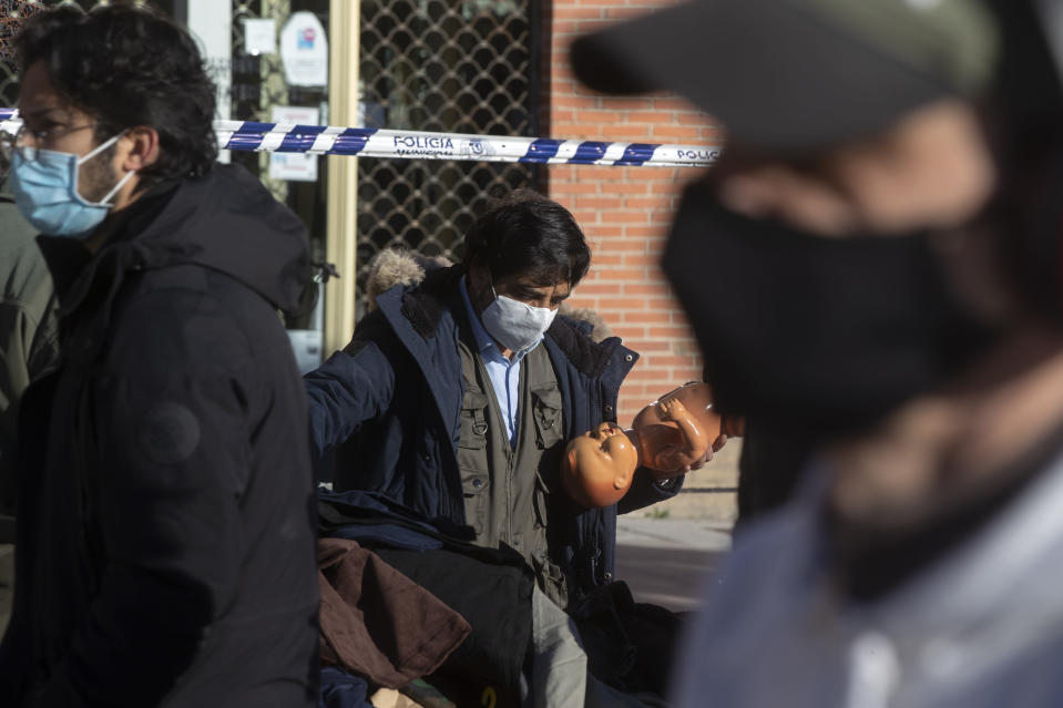 A stall-holder organises his display in the Rastro flea market in Madrid, Spain, Sunday, Nov. 22, 2020. Madrid's ancient and emblematic Rastro flea market reopened Sunday after a contentious eight-month closure because of the COVID-19 pandemic that has walloped the Spanish capital. (AP Photo/Paul White)