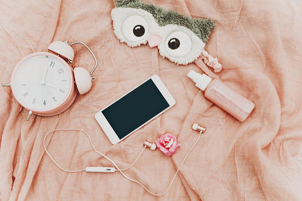 top view alarm clock, sleeping mask, smartphone and beauty feminine items in coral color