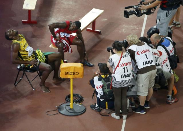 Winner Bolt of Jamaica sits on a chair next to second placed Gatlin of the U.S. after competing at the men's 200 metres final during the 15th IAAF World Championships at the National Stadium in Beijing