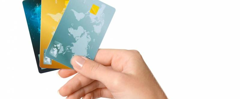 Woman's hand holding credit cards on white background