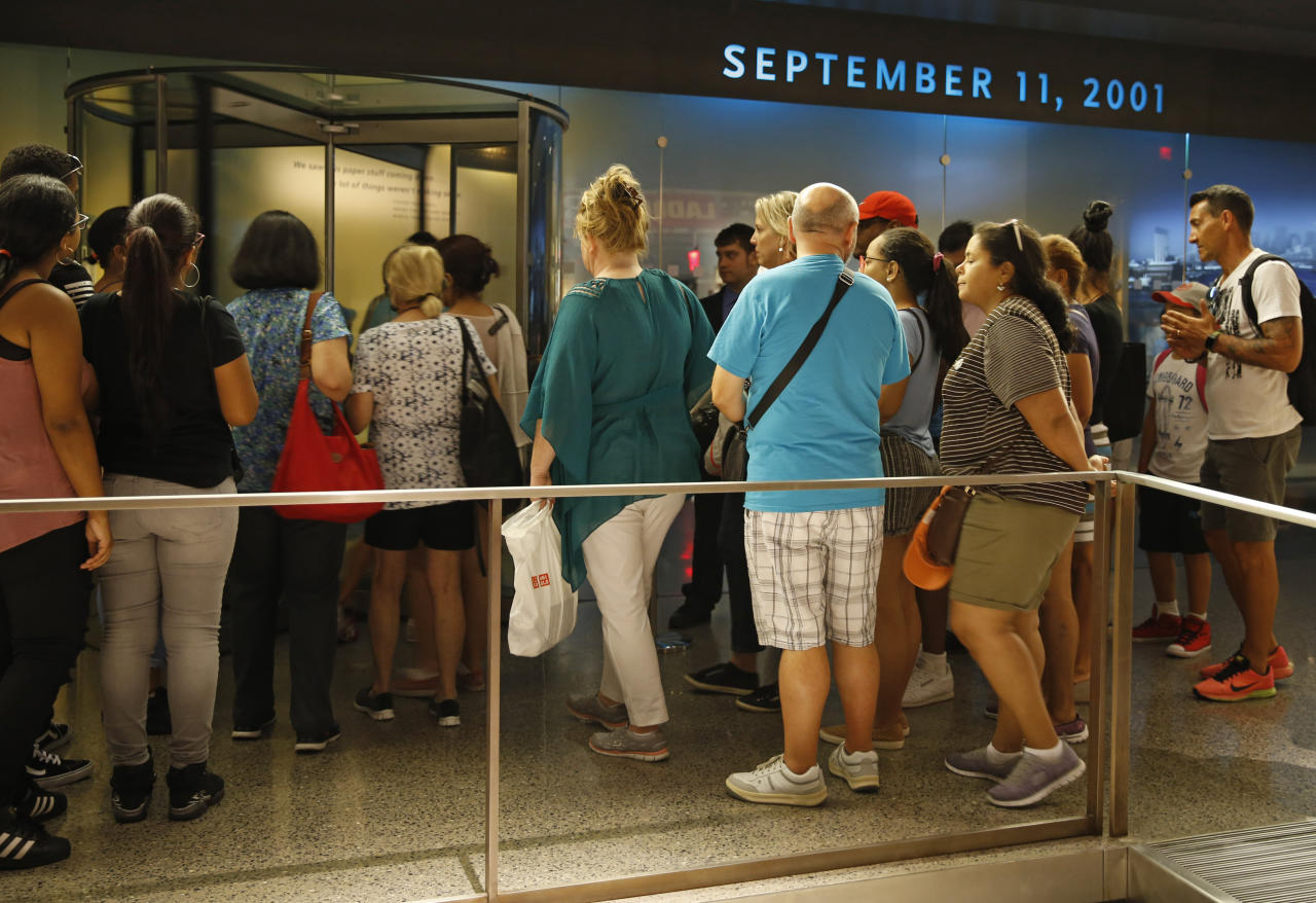 "In this July 11, 2017 photo, visitors to the National September 11 Memorial and Museum line up for entrance to the historical exhibition hall in New York. Last winter the U.S. tourism industry worried about a ""Trump slump,"" fearing that Trump administration policies might discourage international travelers from visiting the U.S. But statistics from the first half of 2017 suggest that the travel to the U.S. is robust and a number of sectors have reported increased international visitation, with one expert calling it a ""Trump bump."" The museum is among those reporting more international visitors this year compared the same period in 2016. (AP Photo/Kathy Willens)"