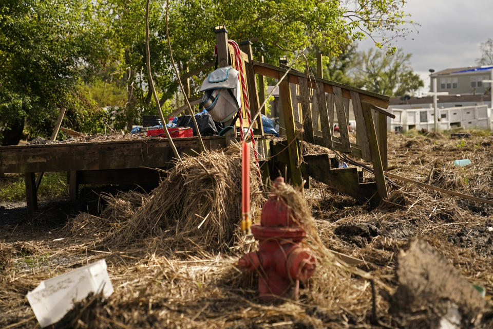 Steps from a destroyed structure sit amid mud and marsh grass from Hurricane Ida flooding, in Ironton, La., Monday, Sept. 27, 2021. Nearby houses are disconnected from their foundations, a refrigerator is lodged sideways in a tree, and dozens of caskets and tombs from two nearby cemeteries are strewn across lawns for blocks. The entire town is without power and running water. (AP Photo/Gerald Herbert)
